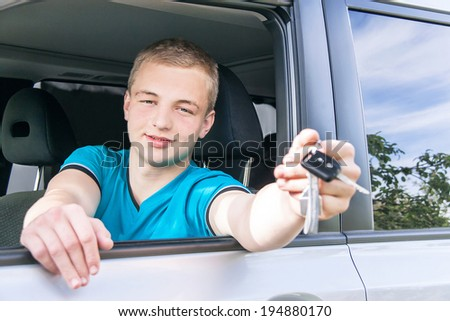 Car driver. Caucasian teen boy showing car key in the new car. Happy smiling young man behind the wheel. Travel and rental concept. Close up, outdoor.