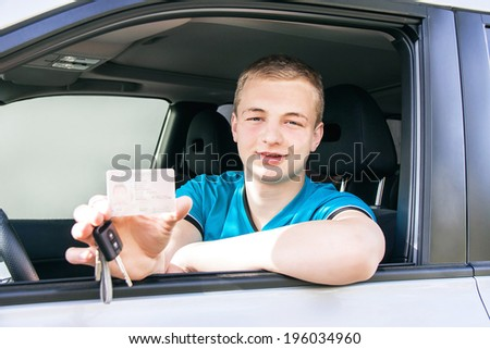 Car driver. Caucasian teen boy showing driver license and new car key in the car window. Happy smiling young man behind the wheel. Travel and rental concept. Close up, outdoor.  - stock photo