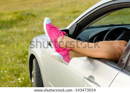 Car driver relaxing and resting on summer travel vacation in nature. Female feet out of vehicle window. - stock photo