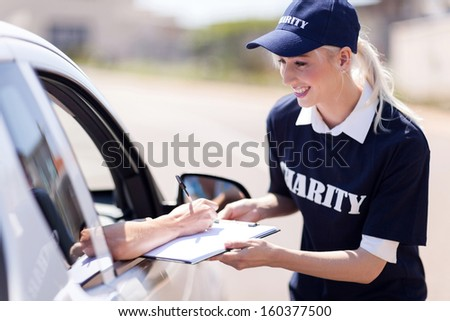 car driver signing a donation papers for charity - stock photo