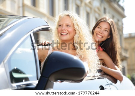 Car driver woman driving with girl friends on road trip travel vacation in convertible car in summer. Happy female driver free lifestyle with two beautiful women girlfriends.