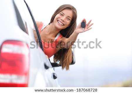 Car driver woman happy showing car keys out window. New car, rental or driving licence concept with young female model on road trip. Mixed race Asian Caucasian girl in her 20s. - stock photo