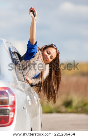 car driver woman smiling showing new car keys   - stock photo