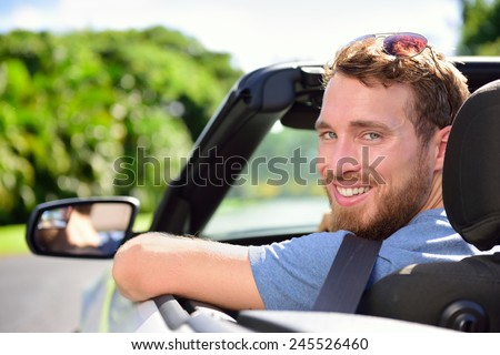 Car driver - young man wearing safety belt driving convertible on road trip in summer. Caucasian male looking at camera. - stock photo
