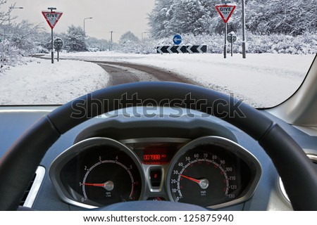 Car drivers view through the vehicle windscreen whilst driving on a snow covered road approaching a roundabout with Give Way signs, the carriageway has one driveable lane formed by previous motorists. - stock photo