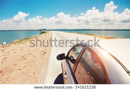 Car driving across ocean by the road - stock photo
