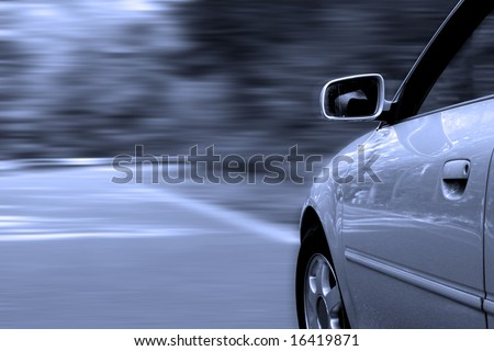 Car driving fast along a countryroad, blurred background, all tuned in blue