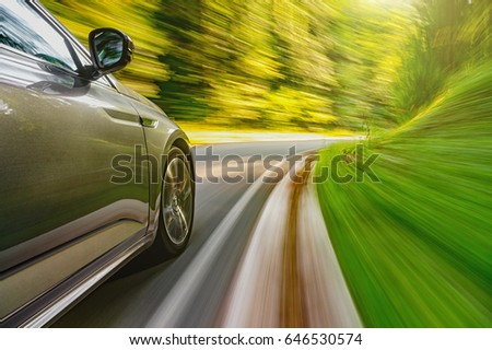 Car driving fast on a mountain road towards setting sun
