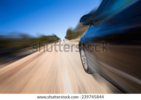 car driving fast on forest road - stock photo