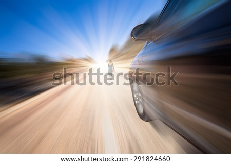 car driving fast on road and A woman walking on the road in a dangerous manner - stock photo