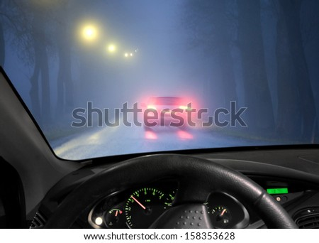 Car driving in a dark avenue in thick fog, seen through windscreen of other vehicle - stock photo
