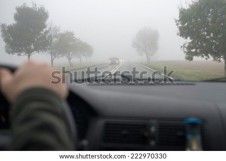 Car driving in thick fog, seen through windscreen of other vehicle - stock photo
