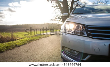 car driving on a asphalt country road with blue sky - front view
