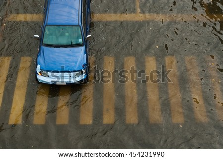 Car driving on a flooded road. - stock photo
