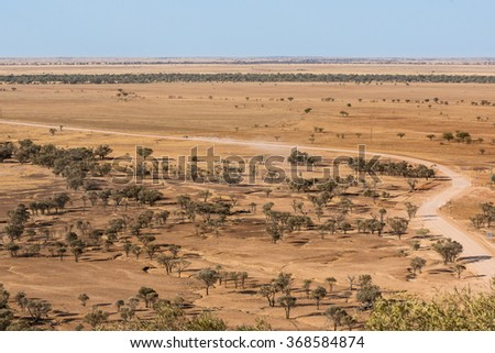 Car driving on dry, dusty road in drought conditions in outback australia, high view point - stock photo
