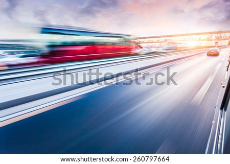 Car driving on freeway at sunset, motion blur - stock photo