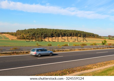 Car driving on highway in sunny weather, motion blur. - stock photo