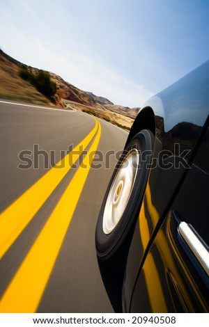 car driving on mountain road - low angle with natural motion blur, focus on wheel - stock photo