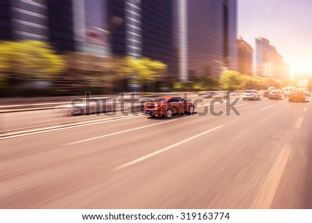 Car driving on road at sunset, motion blur - stock photo