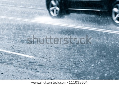 Car driving through in a downpour - stock photo
