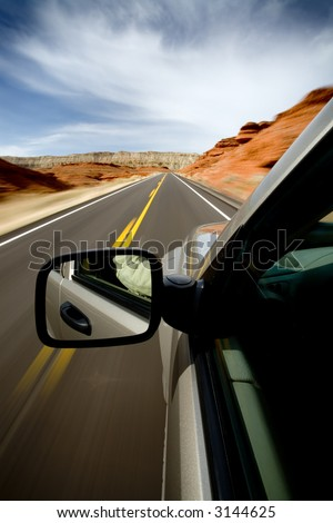 car driving through the Bighorn Canyon, Wyoming, with motion blur. SUV, focus on mirror. - stock photo