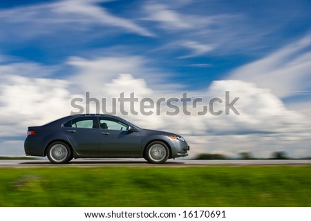 Car drivnig fast. Blue sky and meadow.