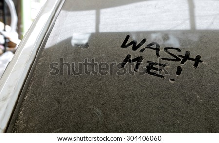 Car dust word on dirty rear window of the car and inscription WASH ME!. Front and side view. Close up of text with handwriting. - stock photo