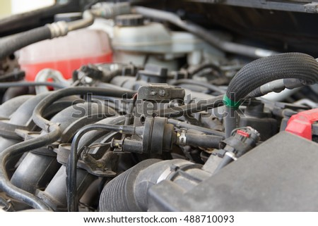 Car engine under the open hood and dust
