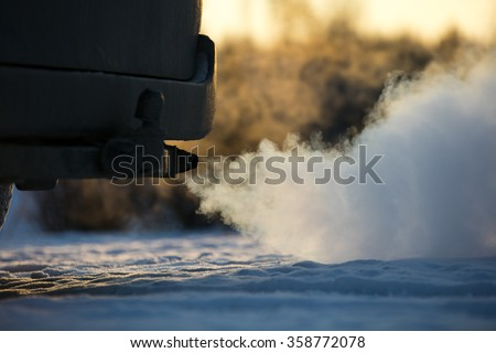 Car exhaust pipe, which comes out strongly of smoke in Finland. Focal point is the center of the photo. Background out of focus.  - stock photo