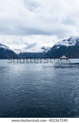 Car ferry by the mountains in a fjord in Norway - stock photo