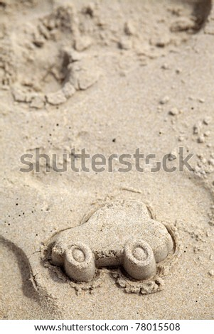 Car figure made of sand on Beach. Traveling by car