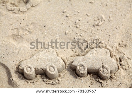 Car figures made of sand on Beach. Traveling by car - stock photo
