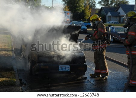Car fire and the efforts to put it out. - stock photo
