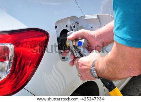 Car fueling nozzle at gas station - stock photo