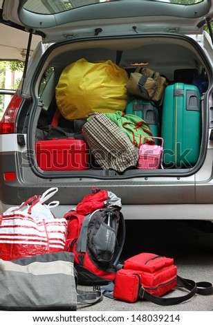 car full of luggage bags and travel bags before the family vacation - stock photo