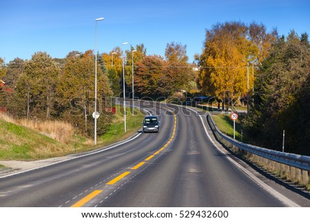 Car goes down the turning rural highway in autumn season, Norwegian countryside