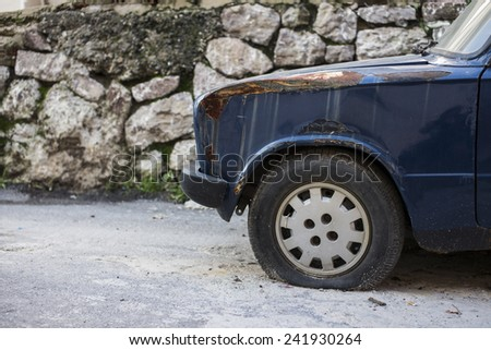 Car has rusted paint and flat tire. - stock photo