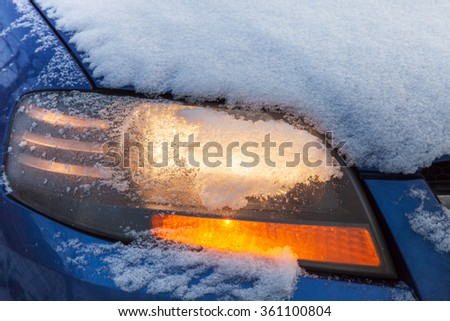 Car headlight flashing under the snow, outdoors close-up - stock photo