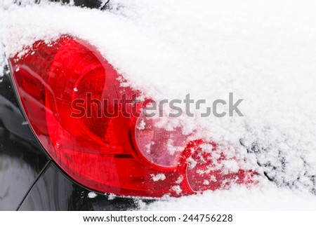 Car headlight in snow, outdoors - stock photo