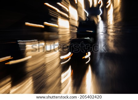 Car headlights at night with a motion blur to illustrate drunk driving. - stock photo