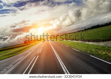 Car Highway at sunset and contrast cloudy sky. - stock photo