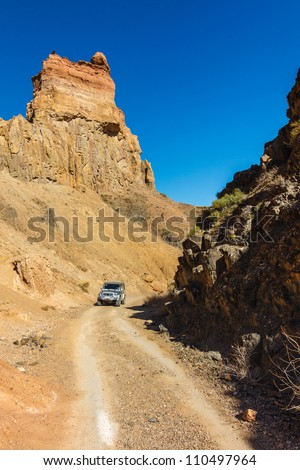 Car in Charyn Canyon near the Almaty city in Kazakhstan - stock photo