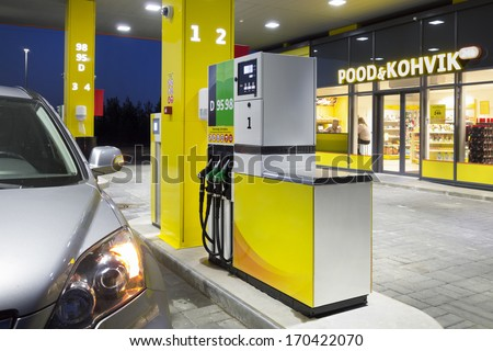 Car in gas station. Fuel, petrol dispenser, pump, handles and pillars. Fueling. Estonia. Lighted window of convenience store and coffe shop. - stock photo