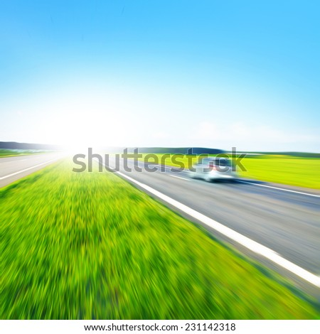 Car in motion blur and sunlight. - stock photo