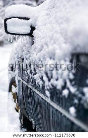 Car in snow and icicles during icing in town - stock photo
