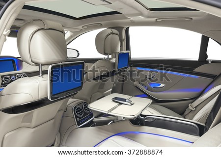 Car inside. Interior of prestige modern car. Back seats with displays, tables & mobile phone. White cockpit with panoramic roof & blue ambient light on isolated white background. - stock photo