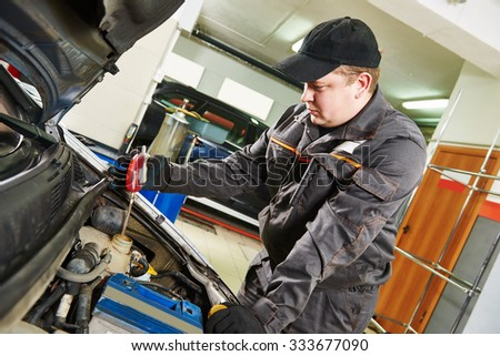 Car inspection. Automobile mechanic using a hydrometer areometer to check the concentration of antifreeze in the coolant at repair service station - stock photo