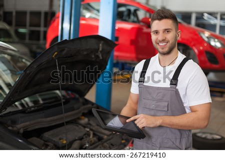 Car inspection. Smiling man in workshop posing with a digital tablet. - stock photo