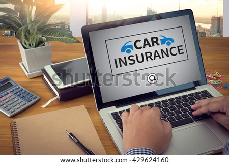 CAR INSURANCE Close up of business man hand working  laptop computer on wooden desk Warm tone - stock photo