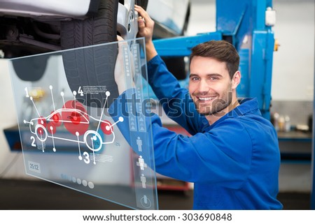 Car interface against mechanic adjusting the tire wheel - stock photo